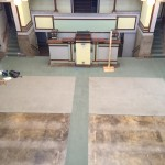 Unity Temple floor. Pews have been removed. Carpet has been removed exposing magensite flooring which will be restored.
