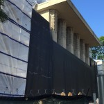 North facade of Unity Temple. The black screen has been added during the drilling of geothermal wells in the north lawn. The white screen is protecting the scaffolding. Once the geothermal wells are complete, the scaffold will continue on the north side.